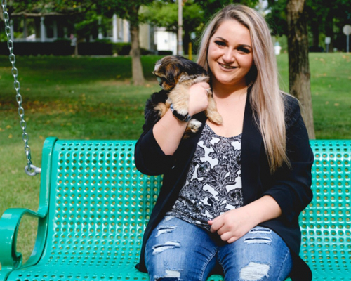 Hannah Garofalo with her puppy sitting on a bench